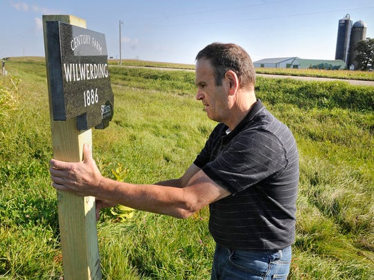Decker installs a century farm marker at the Wilwerding farm . In his 37 years of work at the museum, Decker has certified 446 century farms in Stearns County.