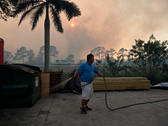 "American Stairs employee Jeff Spencer, of Palm City, wets down lumber and brush lining the businesses' property Wednesday, Feb. 15, 2017, on Southwest Old Kansas Avenue as a brush fire burns behind him across Florida's Turnpike in Martin County. ""I'm protecting my welfare, and my kitty,"" Spencer said, referring to a cat that lives near the business. Multiple fires were aided by windy conditions across Martin and St. Lucie counties."
