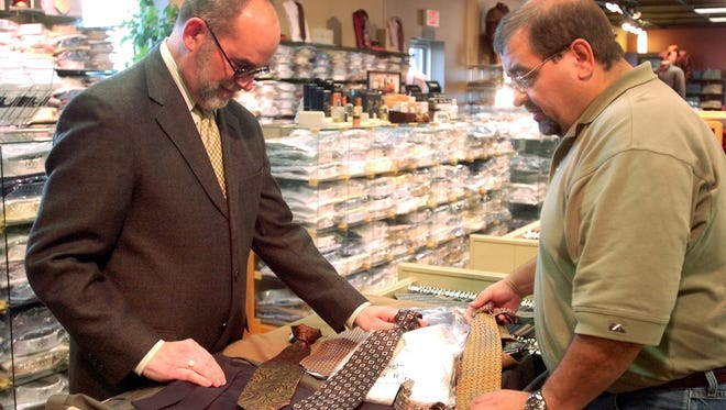 Gary Gaede helps long time Norman's customer Rich Kafka pick out a neck tie at the store on south Minnesota Ave.  (Elisha Page/Argus Leader)