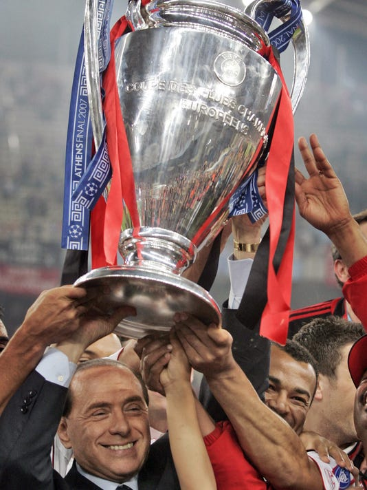 FILE - In this file photo taken in Athens on May 23, 2007, AC Milan's Silvio Berlusconi raises the trophy aloft as he stands with his team after they beat Liverpool 2-1 to win the Champions League Final soccer. The takeover of AC Milan has been completed Thursday, April 13, 2017, with Silvio Berlusconi selling the club to a Chinese consortium after 31 years in charge. (AP Photo/Murad Sezer)