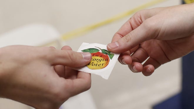 A polling attendant hands a Georgia Voter sticker to a voter during the 2019 November election. Voters heading to the polls Tuesday will find special procedures in place, and some in Athens-Clarke County will also be heading to new polling places.