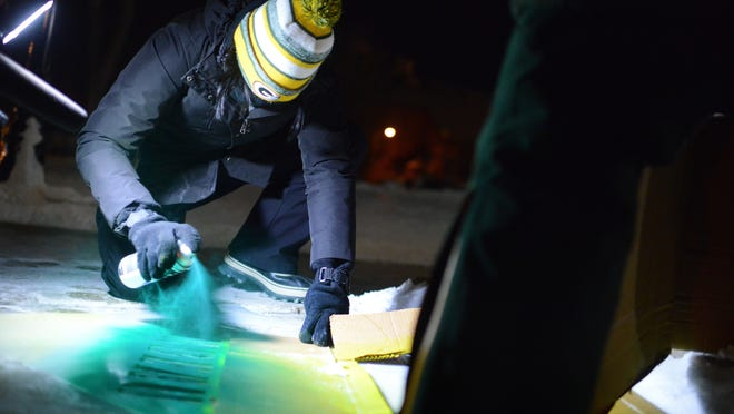 Gabrielle Valdez Dow, the Green Bay Packers Vice President of Marketing and Fan Engagement, sprays chalk on a 'Get Loud Lambeau' stencil outside the Brown County Courthouse in Green Bay on Wednesday.
