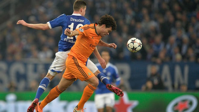 Real's Pepe, right and Schalke's Julian Draxler challenge for the ball during a Champions League round of sixteen, first leg soccer match between Schalke 04 and Real Madrid at the Veltins Arena in Gelsenkirchen, Germany.