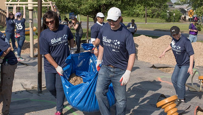 BlueCross employees Candace Featherstone and Scott Pierce carry mulch during a KaBOOM! workday at Hope for the Inner City in Chattanooga, Tenn.