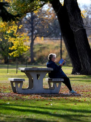 Shirley Coe reads in Gibson Park in mild autumn weather.