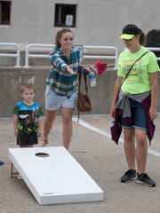 Players compete in a cornhole tournament during the Backyard Burgers and Brew event in downtown Battle Creek on August 25, 2018.