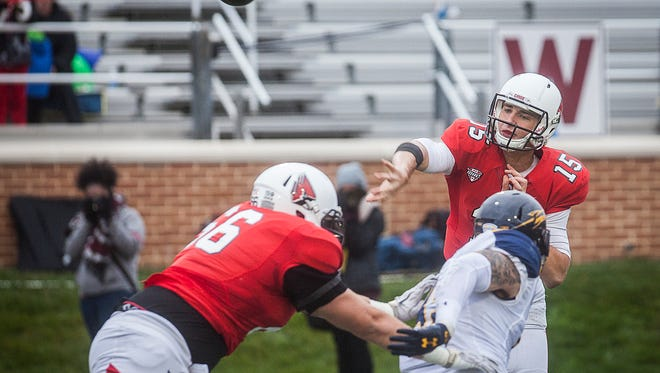 Ball State's Riley Neal passes past Toledo's defense during their game at Scheumann Stadium Saturday, Oct. 3, 2015.