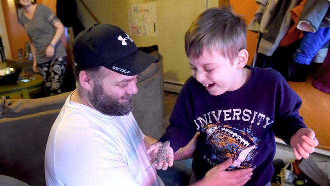 """Hudsen Wolfe, 7, can't contain his laughter as he shows his father, John, """"Gizzy"""" the bearded dragon, in their West York home. Hudson, was diagnosed with a  brain tumor known as diffuse intrinsic pontine glioma or DIPG for short. The West York community has rallied to help the family."""