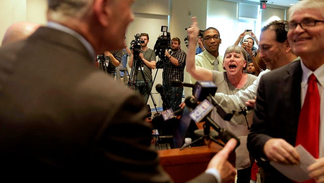 CORRECTS CITY - A woman, center, screams about her child's health care, which she says is threatened, as Sen. Bill Cassidy, left, enters his town hall meeting at East Jefferson Regional Library in Metairie, La., Wednesday, Feb. 22, 2017. (Andrew Boyd/NOLA.com The Times-Picayune via AP)