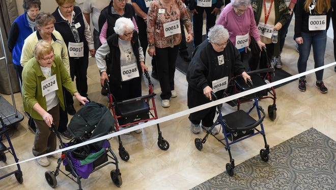 Residents cross the finish line after completing a combined equivalent of two marathons during a celebration of the Boston Marathon Monday, April 16, at The Sanctuary at St. Cloud assisted living and memory care facility.