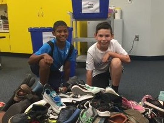 Jalen Sutton, 11, and Ty Lendino, 11, help package