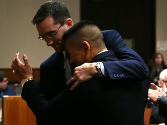 Charles Tan is hugged by attorney Brian DeCarolis after