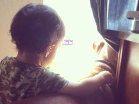 Our son stares out the window with Ratchet