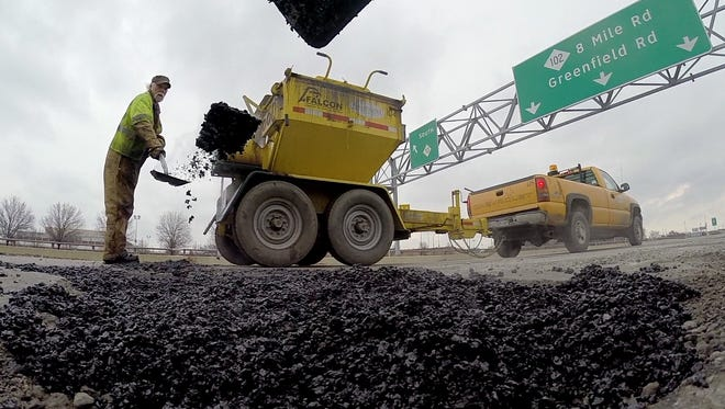 Jim Polk, 62, of Inkster and a road maintenance worker at the city of Southfield throws another shovel of hot asphalt to the pile to fill a pothole on Northwestern Highway in Southfield on Saturday, March 29, 2014.