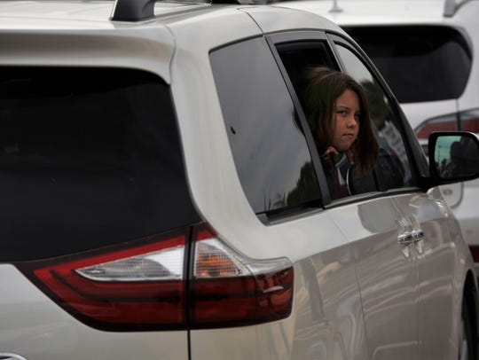 Kylie Browning, 10, looks out a window as she waits for the seventh-grade students Thursday outside Wylie Middle School. The middle school and junior high school share the same parking lot.