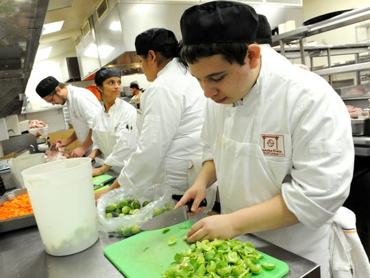 Daniel Gonzalez cuts artichokes with other students in Rancho Cielo's Drummond Culinary Academy as they prepare food for the Castroville Community Feast on Thanksgiving.