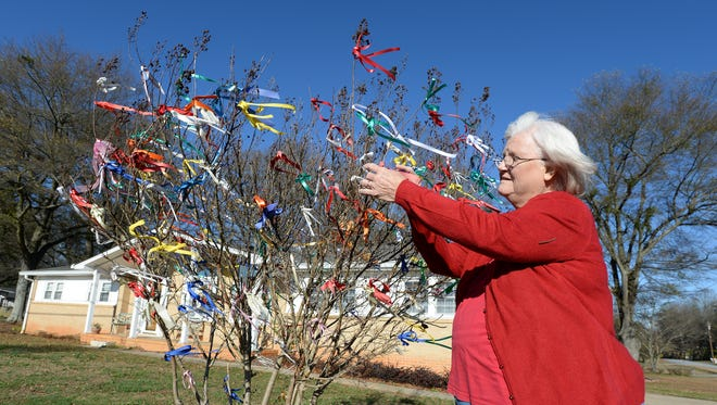 Tina Delk places ribbons on her prayer tree in the front yard of her Greenville home Friday, December 18, 2015. Delk places color ribbons on the tree when she receives prayers requests and places white ribbons when the prayers are answered.