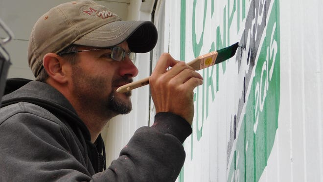 Barn artist Scott Hagan works on the finishing touches for his Ohio Turnpike mural. The mural celebrates the turnpike's 60th anniversary. Rutherford B. Hayes was also painted on the barn on Fangboner Road, next to the Ohio 53 turnpike exit.