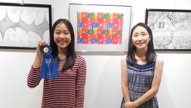 Jaeryung Park and her mother in front of her award winning artwork.
