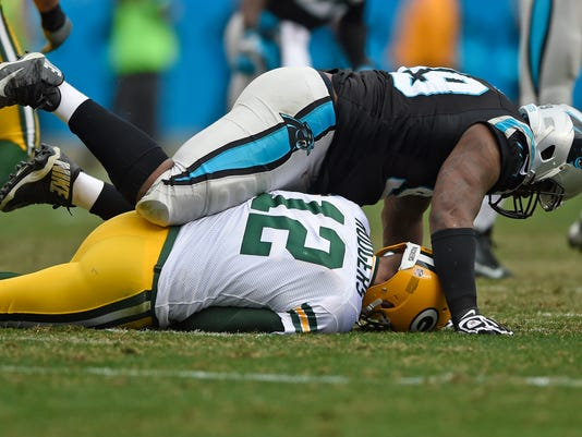 Carolina Panthers' Kawann Short (99) falls onto Green Bay Packers' Aaron Rodgers (12) during the second half of an NFL football game in Charlotte, N.C., Sunday, Dec. 17, 2017. (AP Photo/Mike McCarn)