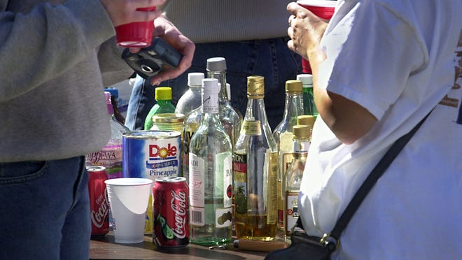 SEP29/01 CAMPUSBOOZE (63203) Photo/Frank Espich :::::: Pictured here a table full (of practically empty) booze bottles and mixes surrounded by students at Indiana University during one of the many after game parties where large amounts of alcohol is consumed. This particular party area located across the street from IU's Memorial Stadium (in Bloomington) is one of the more popular spaces for after football games. *FOR A GEORGE STUTEVILLE CITY STATE STORY ON CAMPUS BOOZE*