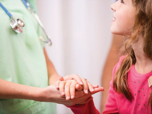 Nurse or doctor consoles, holds hand of child patient.