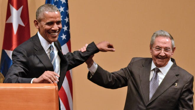 "Cuban President Raul Castro raises President Obama's hand during a joint press conference at the Revolution Palace in Havana on Monday. Castro stood next to Barack Obama and hailed his opposition to a long-standing economic ""blockade,"" but said it would need to end before ties are fully normalized."