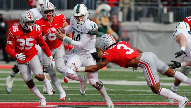 Michigan State quarterback Brian Lewerke, center, runs the ball as Ohio State cornerback Damon Arnette, right, makes the tackle during the first half of an NCAA college football game Saturday, Nov. 11, 2017, in Columbus, Ohio.