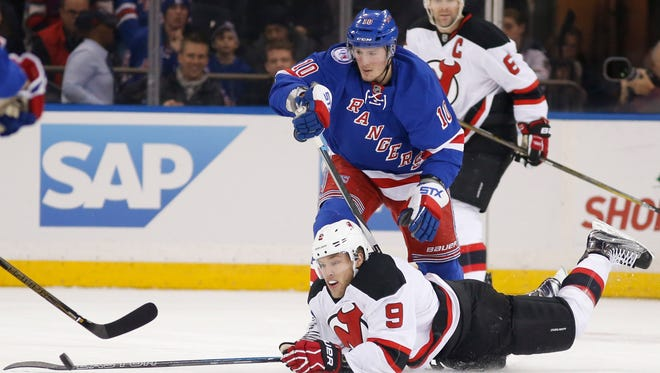 Rangers left wing J.T. Miller (10) watches as Devils left wing Taylor Hall (9) tries to control the puck after falling to the ice during a December game.