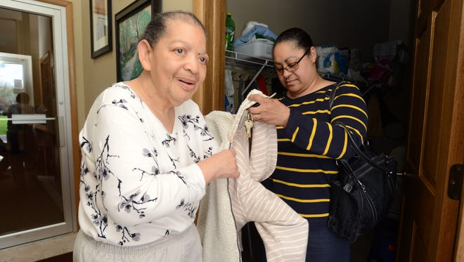 Denise Brown helps her cousin, Irene Collins, into her coat at the Carr Center. Brown drops Collins, who has Down syndrome, off at the center's adult day care program so she can go to work.