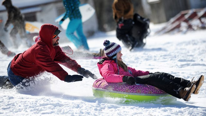 """Mike Starling, left, gives his daughter Valerie a push on her tube as locals take to """"the hill"""" behind Onancock School for sledding fun after Tuesday's snow on Feb. 17, 2015."""