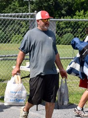 Volunteer Randy Yount carries food for the concession
