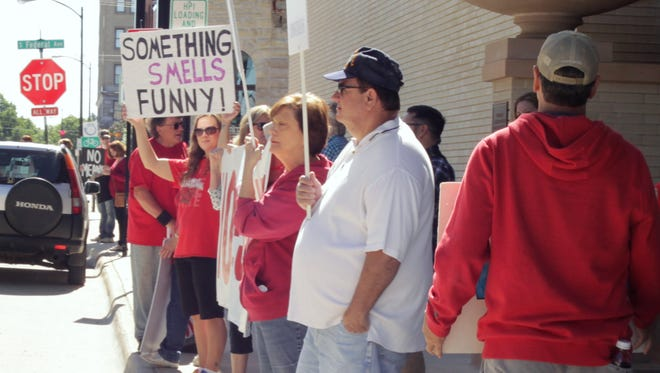 Protesters line the sidewalks, chanting at motorists to honk, in front of the Frank Lloyd Wright Hotel in downtown Mason City in May. They had gathered to express their opposition to the $240 million pork processing plant in Mason City proposed by Prestage Farms. The project failed in Mason City in May, and the company has proposed locating it in Wright County, south of Eagle Grove.