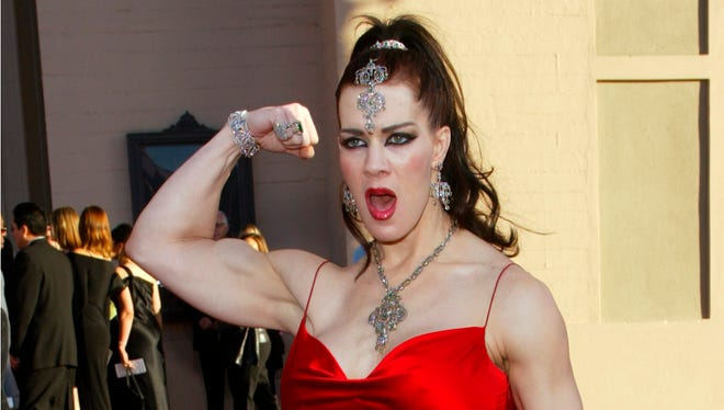 In this Nov. 16, 2003 file photo, Joanie Laurer, former pro wrestler known as Chyna, flexes her bicep as she arrives at the 31st annual American Music Awards, in Los Angeles. Chyna, the WWE star who became one of the best known and most popular female professional wrestlers in history in the late 1990s, has died at age 46. Los Angeles County coroner's Lt. Larry Dietz says Chyna, whose real name is Joan Marie Laurer, was found dead in Redondo Beach on Wednesday.