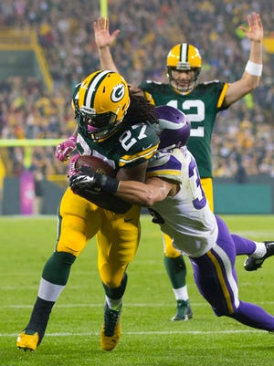 Aaron Rodgers gives the signal in the background as Eddie Lacy rumbles into the end zone for a third-quarter TD.