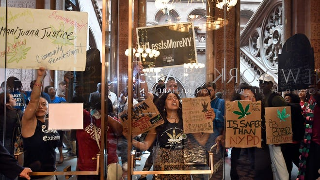 Protesters urging lawmakers to pass marijuana legislation hold signs against the state Senate lobby doors June 19 at the state Capitol in Albany.