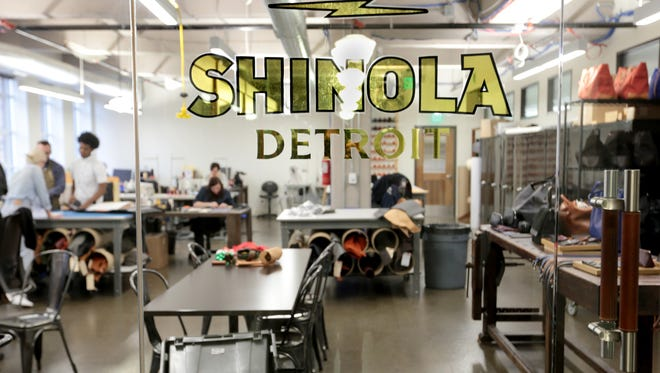 Designers for leather goods can be seen behind the Shinola Detroit sign at their factory in Detroit on Friday, December 11, 2015.