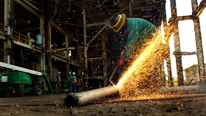 Welder Antonio Miranda cuts a pipe into sections for recycling in April 2009 as crewmen prepare the north side of the H.D. King Power Plant in Fort Pierce for a section of the roof and its support beams to be torn down.