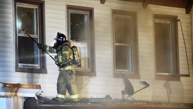 A Lebanon firefighter, wearing a Self-Contained Breathing Apparatus, battles flames from a rooftop at 430 N. Ninth Street in Lebanon in April 30.