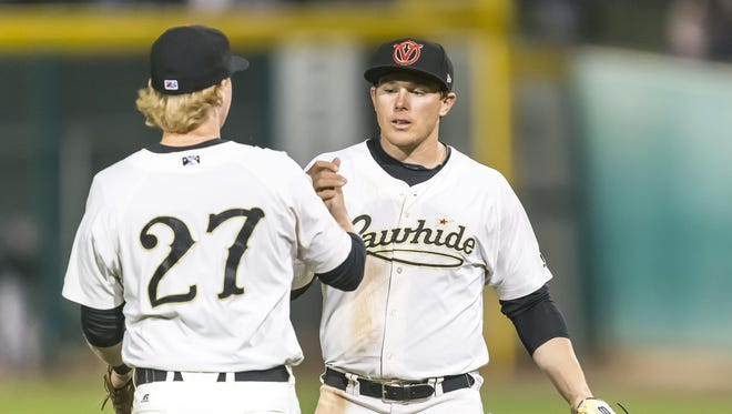 Visalia Rawhide's Marty Herum, 27, and Austin Byler celebrate the team's win game against the Inland Empire during its home opener on Thursday, April 13, 2017.