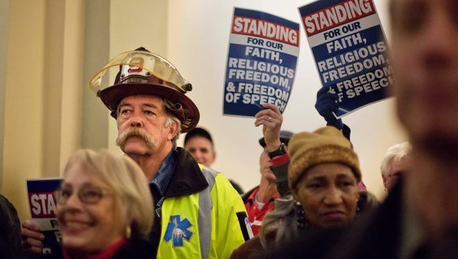 In this Jan. 13, 2015 photo, Michael O'Hara, a retired Fulton County firefighter and current Coweta County paramedic attends a rally to support former Atlanta fire chief Kelvin Cochran following his termination in Atlanta.
