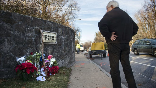 A man stops Dec. 29, 2014, to look at a memorial on Roland Avenue in Baltimore where a cyclist was struck and killed two days earlier.