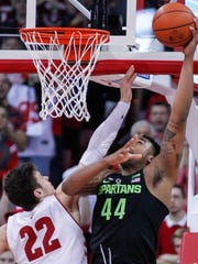 Michigan State's Nick Ward shoots against Wisconsin's Ethan Happ during the second half Sunday, Feb. 25, 2018 in Madison, Wis.