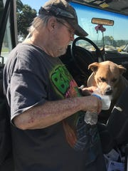 David Pitt of Happy Valley gives his thirsty dog, Buttercup, with a drink of water Thursday at the Red Cross evacuation shelter at West Valley High School.