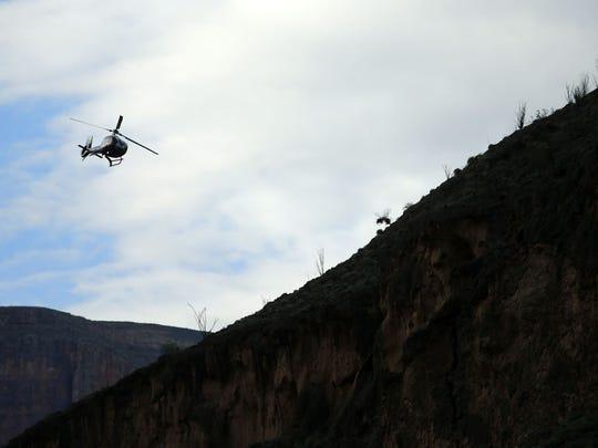 A helicopter flies over the Colorado River through