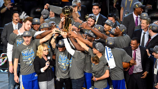 The Golden State Warriors celebrate with the Larry O'Brien Championship Trophy.
