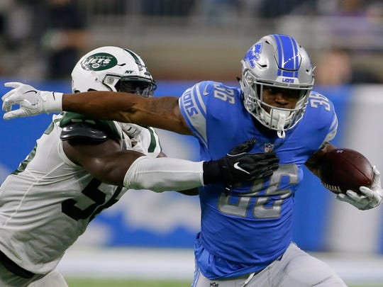 Lions running back Dwayne Washington tries to avoid Jets linebacker Demario Davis in the first half of an exhibition game Aug. 19, 2017 in Detroit.