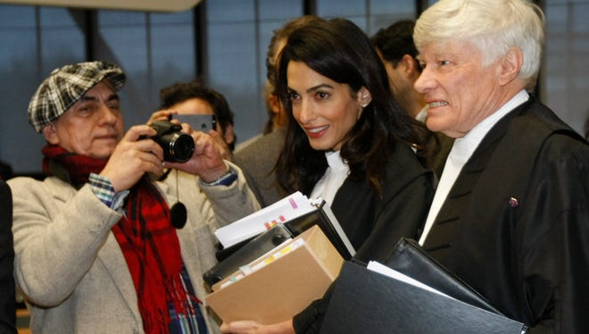 Geoffrey Robertson, right, and Amal Clooney, center, members of a legal team representing Armenia, arrive at the European Court of Human rights in Strasbourg, eastern France, Wednesday, Jan. 28, 2015.