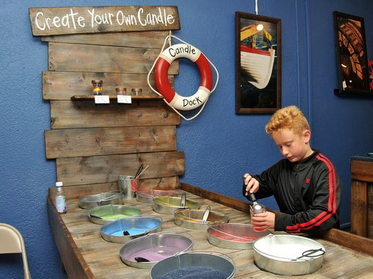 """Kayden Thebeau, 8, of Port Clinton, creates his own candle at the candle dock at Northern Exposure Gallery on during the Greater Port Clinton Area Arts Council's """"Art Walk"""" in Port Clinton, October 2015."""