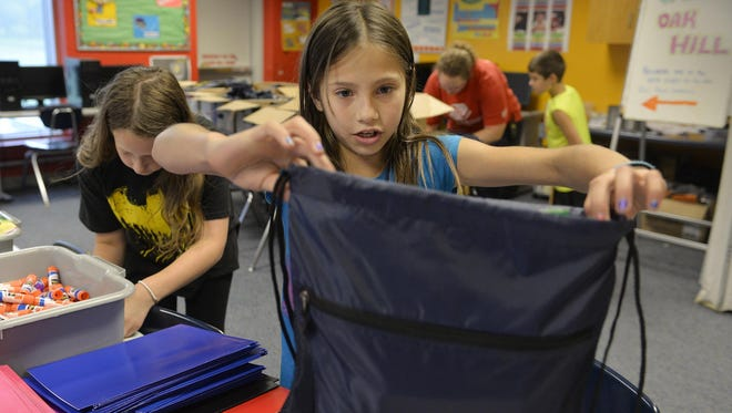 Southside Boys & Girls Club member volunteer McKayla Vick, 10, shimmies a notebook into place inside a backpack Tuesday as she and other young volunteers help create kits of donated school supplies for other needy students at the club in St. Cloud.